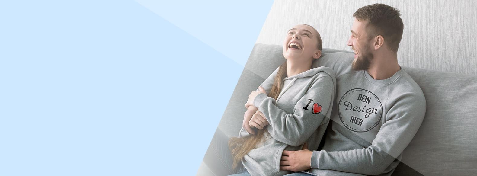 Ein Paar in eigenen Hoodies sitzt auf einem Sofa